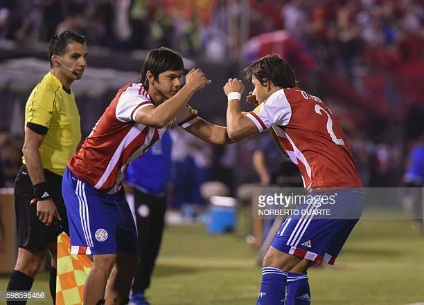 Paraguay's midfielder Oscar Romero celebrates with teammate after scoring against Chile the FIFA World Cup 2018 qualifier football match between...