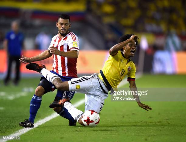 Paraguay's Miguel Samudio and Colombia's Juan Cuadrado vie for the ball during their 2018 World Cup football qualifier match in Barranquilla Colombia...