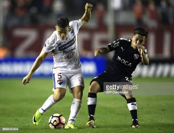 Paraguay's Nacional midfielder Edgardo Orzusa vies for the ball with Argentina's Independiente midfielder Ezequiel Barco during their Copa...