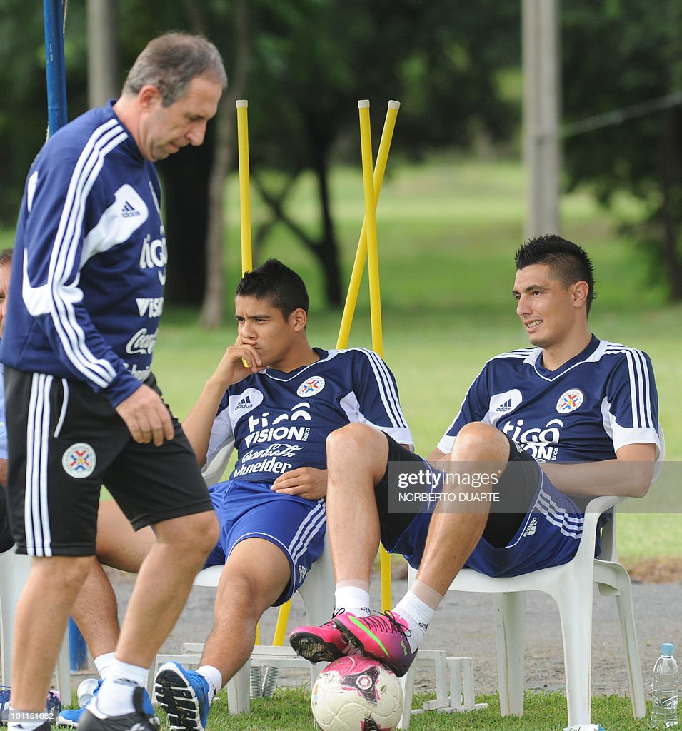 Paraguay's national football coach Uruguayan Gerardo Pelusso (L) walks next to players Lorenzo Melgarejo (C) and Oscar Cardozo during a a training session in Ypane, near Asuncion, on March 20, 2013 . Paraguay will face Uruguay on March 22 for a FIFA World Cup Brazil 2014 qualifier tournament match. AFP PHOTO/NORBERTO DUARTE