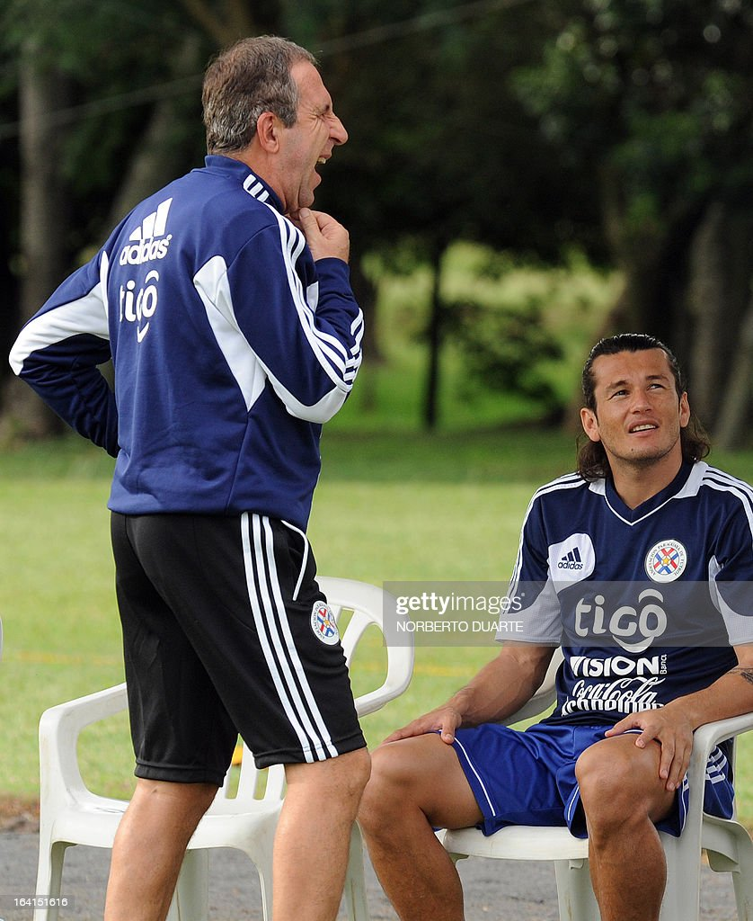 Paraguay's national football team coach Uruguayan Gerardo Pelusso (L) gestures a he speaks with his players next to Haedo Valdez during a training session in Ypane, near Asuncion, on March 20, 2013 . Paraguay will face Uruguay on March 22 for a FIFA World Cup Brazil 2014 qualifier tournament match. AFP PHOTO/NORBERTO DUARTE