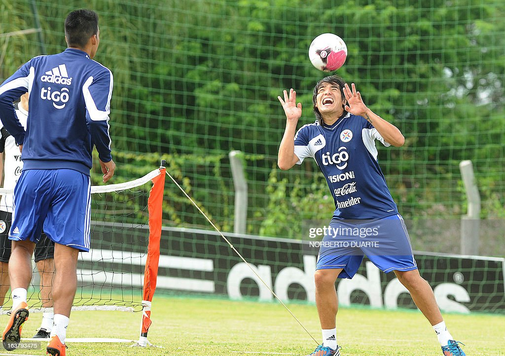 Paraguay's national football team players Videncio Oviedo (R) and Julio Dos Santos Sa take part in a training session in Ypane, near Asuncion, on March 16, 2013 . Paraguay will face Uruguay on March 22 for a FIFA World Cup Brazil 2014 qualifier match.