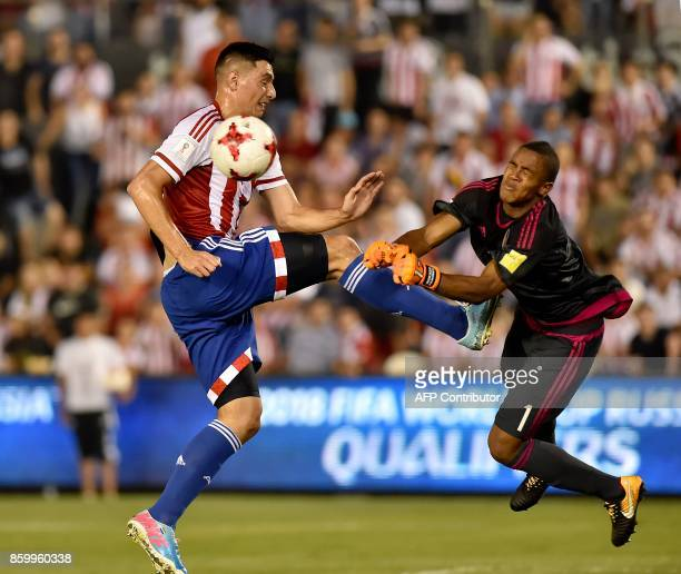 Paraguay's Oscar Cardozo fights for the ball against Venezuela's goalkeeper Wuilker Farinez during their 2018 World Cup football qualifier match in...