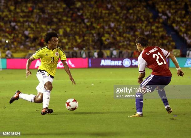 Paraguay's Oscar Romero and Colombia's Juan Cuadrado vie for the ball during their 2018 World Cup football qualifier match in Barranquilla Colombia...