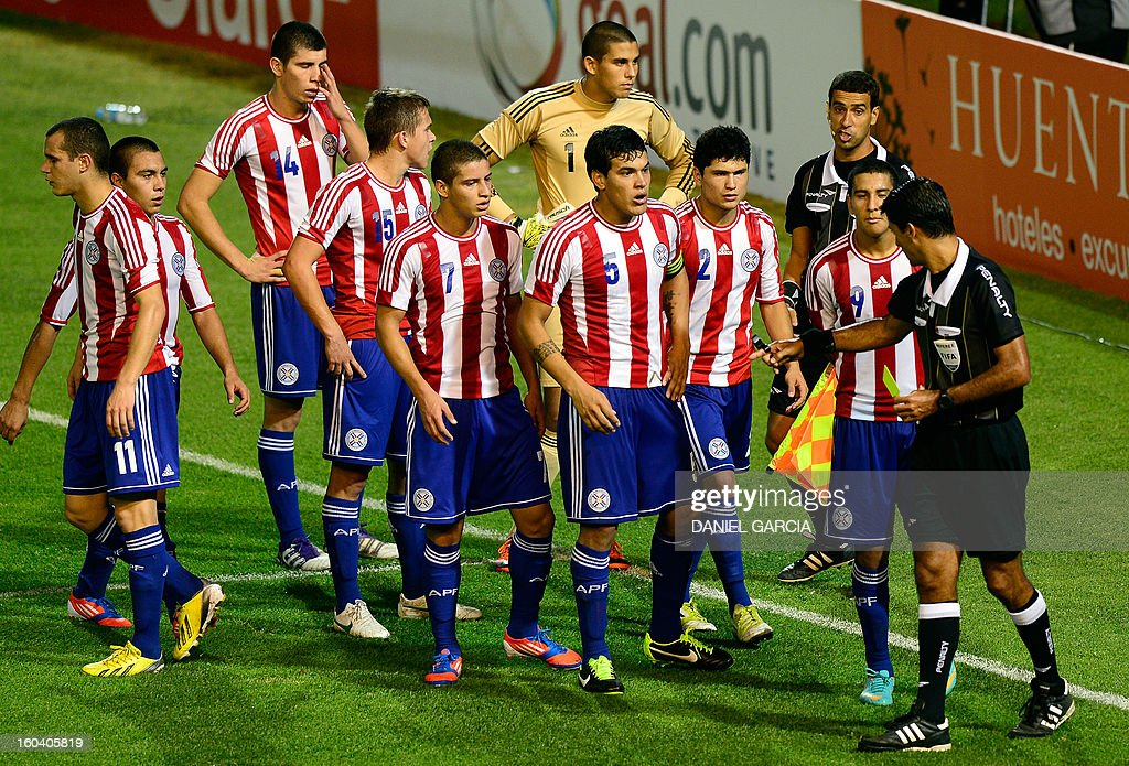 Paraguay's players complain to Brazilian referee Sandro Ricci after he ruled a penalty kick in favor of Uruguay during the South American U-20 final round football match against Paraguay at Malvinas Argentinas stadium in Mendoza, Argentina, on January 30, 2013. Four teams will qualify for the FIFA U-20 World Cup Turkey 2013. AFP PHOTO / DANIEL GARCIA