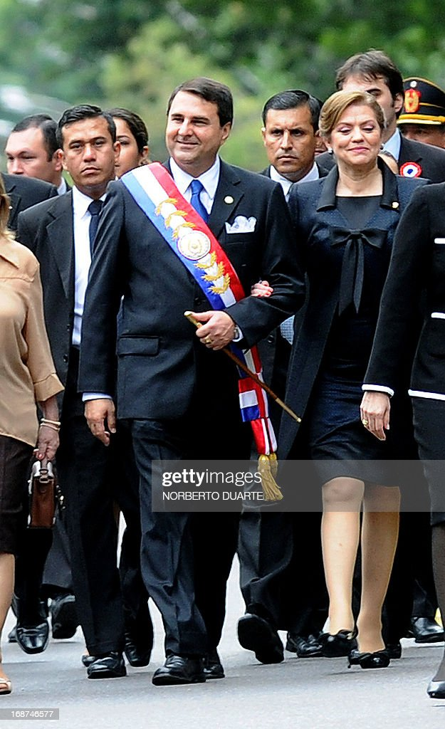 Paraguay's President Federico Franco and his wife Emilia Alfaro walk upon arrival at a military parade celebrating the 202nd Independence anniversary...