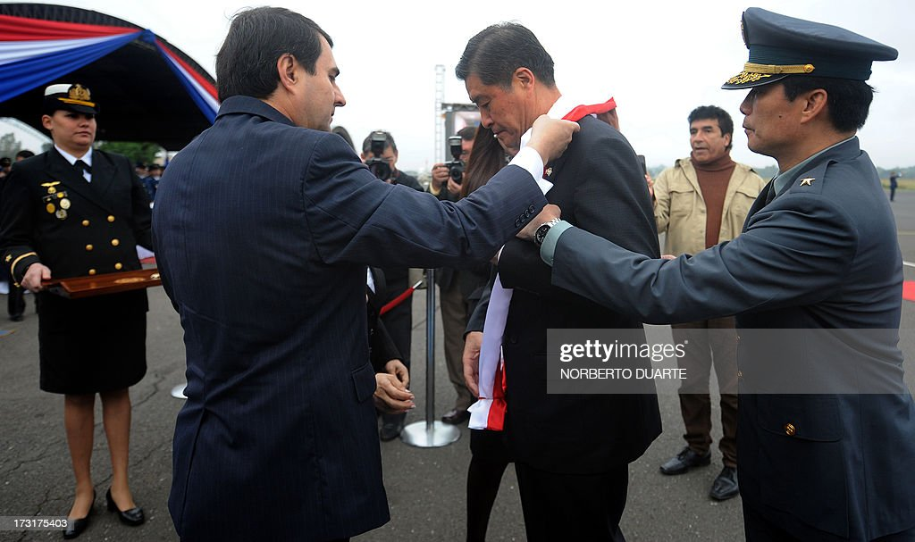 Paraguay's President Federico Franco decorates Taiwan's Defence Minister Kao Huachu with the Military Merit Order medal on July 9 2013 at the airport...