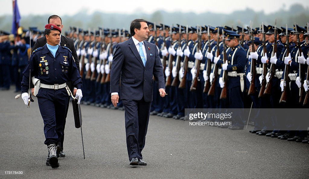 Paraguay's President Federico Franco reviews the troops after Taiwan's Defence Minister Kao Huachu landed on July 9 2013 at the airport in Luque...