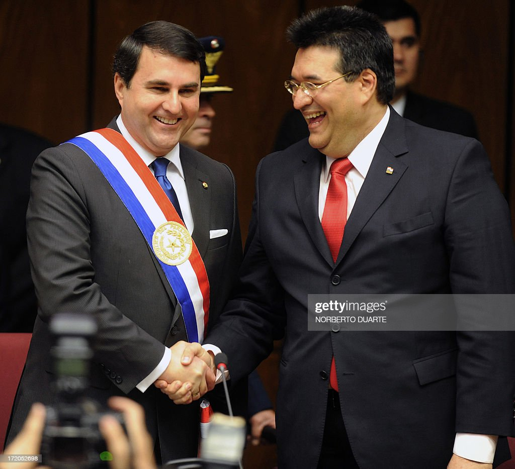Paraguay's President Federico Franco shakes hands with Congress President Julio Velazquez before the delivery of the annual legislative report in...