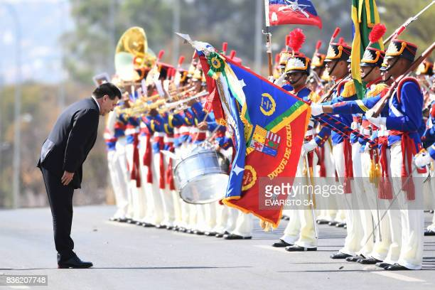 TOPSHOT Paraguay's President Horacio Cartes reviews the honour guard during his welcoming ceremony at Planalto Palace in Brasilia on August 21 2017...