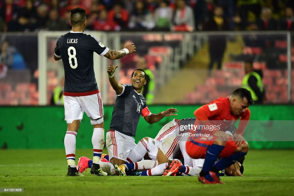 Paraguay's Richard Ortiz (covered) celebrates with teammates after scoring against Chile during their 2018 World Cup qualifier football match, in Santiago, on August 31, 2017. / AFP PHOTO / Martin BERNETTI