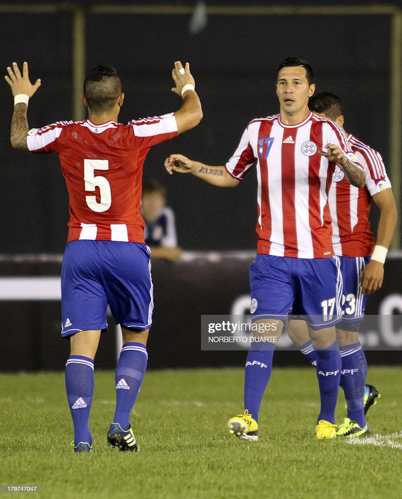 Paraguay's Victor Ayala (L) celebrates with teammate Jonathan Fabbro (R) after scoring against Bolivia during their FIFA World Cup Brazil 2014 qualifying football match at Defensores del Chaco stadium in Asuncion, Paraguay on September 6, 2013.