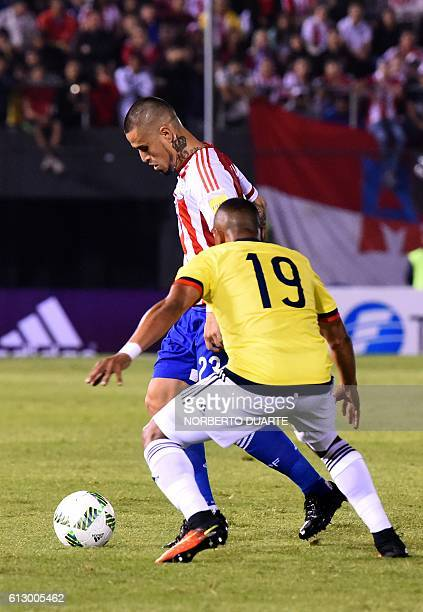Paraguay's Victor Ayala is marked by Colombia's defender Farid Diaz during their Russia 2018 World Cup football qualifier match in Asuncion on...