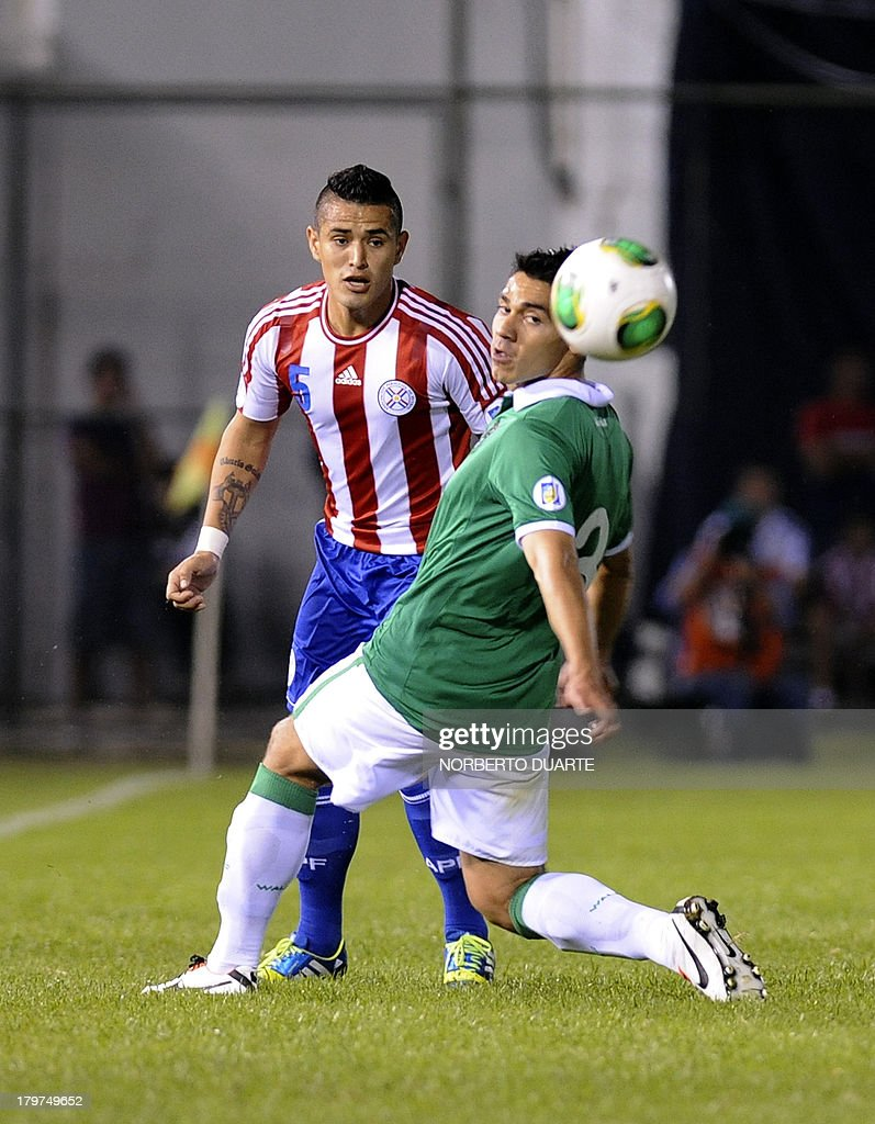 Paraguay's Victor Ayala (L) vies for the ball with Bolivia's Luis Gutierrez during their FIFA World Cup Brazil 2014 qualifying football match at Defensores del Chaco stadium in Asuncion, Paraguay on September 6, 2013. AFP PHOTO/NORBERTO DUARTE