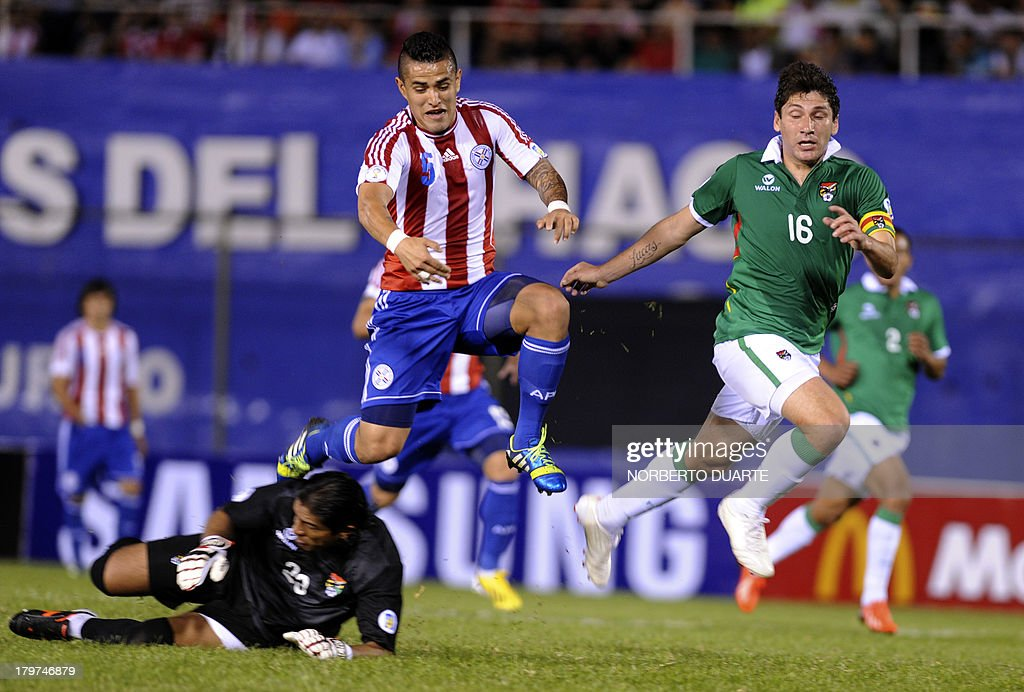 Paraguay's Victor Ayala (C) vies with Bolivia's Ronald Raldes (R) and Sergio Galarza (L) during their FIFA World Cup Brazil 2014 qualifying football match at Defensores del Chaco stadium in Asuncion, Paraguay on September 6, 2013. AFP PHOTO/NORBERTO DUARTE