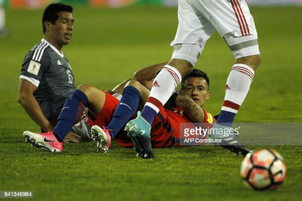 Paraguay's Victor Caceres and Chile's Charles Aranguiz lie on the ground during their 2018 World Cup qualifier football match in Santiago on August...