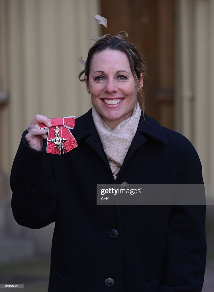 Paralympian Helena Lucas poses for photographs after she received an MBE at Buckingham Palace in London on March 12, 2013. AFP PHOTO/POOL/Stefan Rousseau