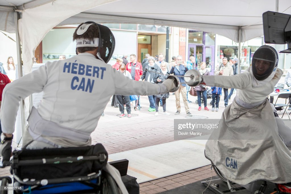Paralympians Camille Chai (R) and Matthieu Hebert demonstrate wheelchair fencing during an outdoor demonstration on Sparks Street during the Medley on the Street event on April 20, 2017 in Ottawa, Canada. The Medley on the Street event promotes Fencing Week in Canada and the upcoming National Canadian Fencing Championships.