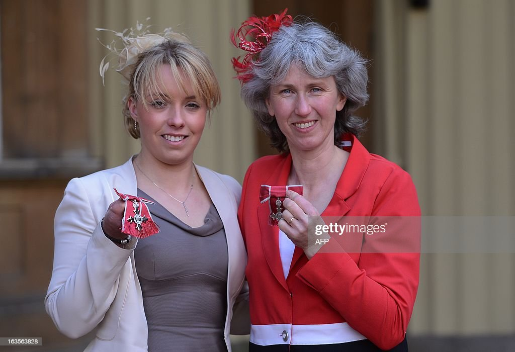 Paralympians Sophie Wells (L) and Deborah Criddle pose for photographs after they received an MBE's at Buckingham Palace in London on March 12, 2013. AFP PHOTO/POOL/Stefan Rousseau