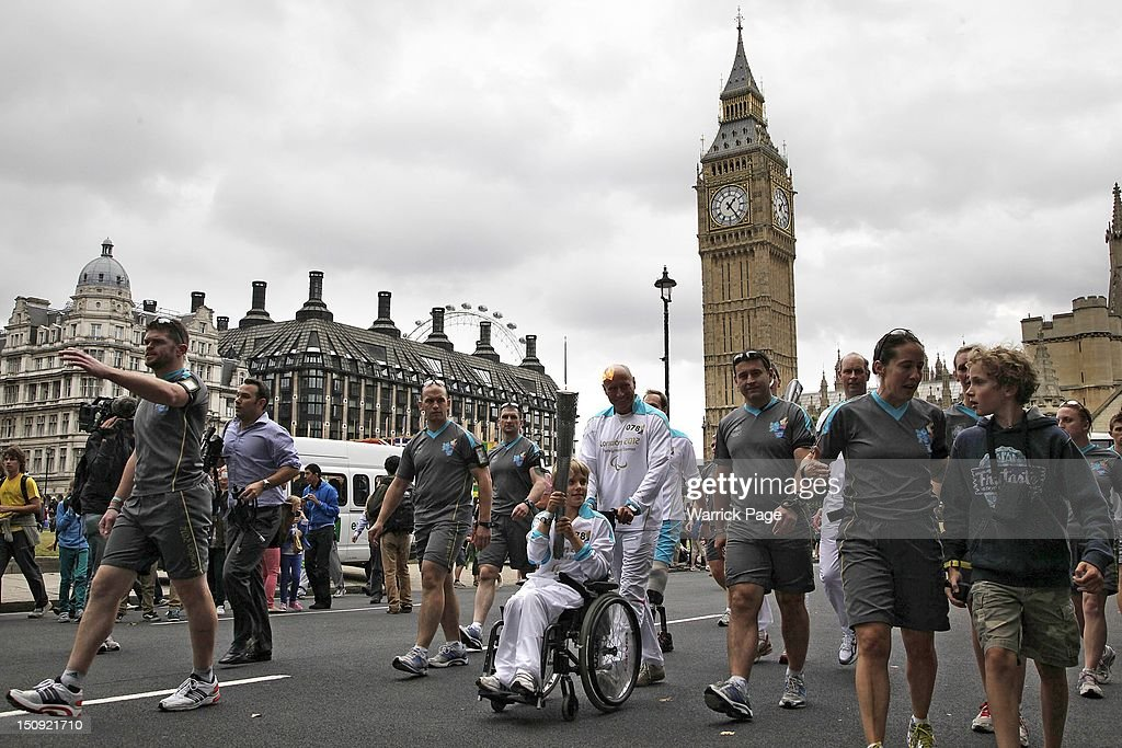 A Paralympic torchbearer carries an Paralympic Torch ahead of the start of the London 2012 Paralympic Games, past Big Ben into Parliament Square on August 29, 2012, in London, England.