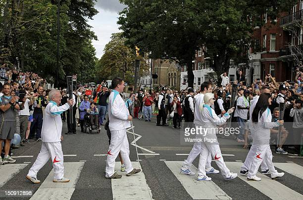 Paralympic Torchbearers Ken Maidens Graham Helm Ketaki Vaidya and Lucy Priest carry Paralympic torches across the Abbey Road pedestrian crossing made...