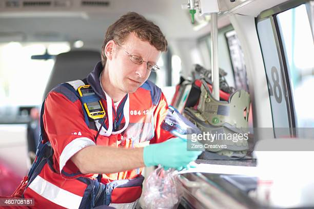 Paramedic in ambulance checking equipment list