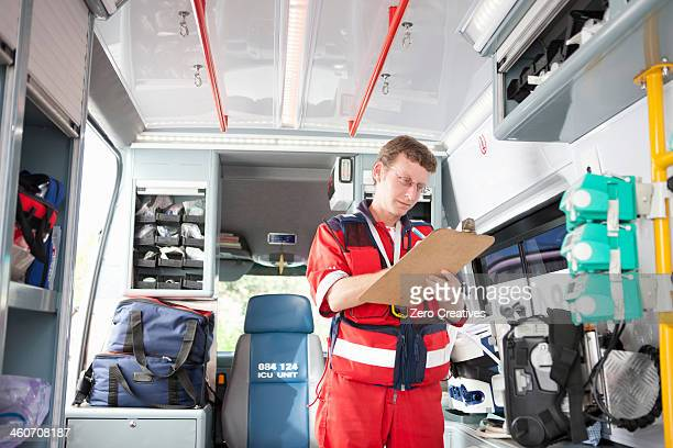 Paramedic in ambulance listing equipment