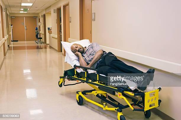 Auxiliaire médical une bonne nuit de sommeil sur un lit d'hôpital dans un couloir de l'hôpital