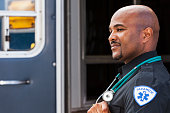 Close up of male paramedic (40s, mixed race African American and Hispanic) standing at rear door of ambulance.