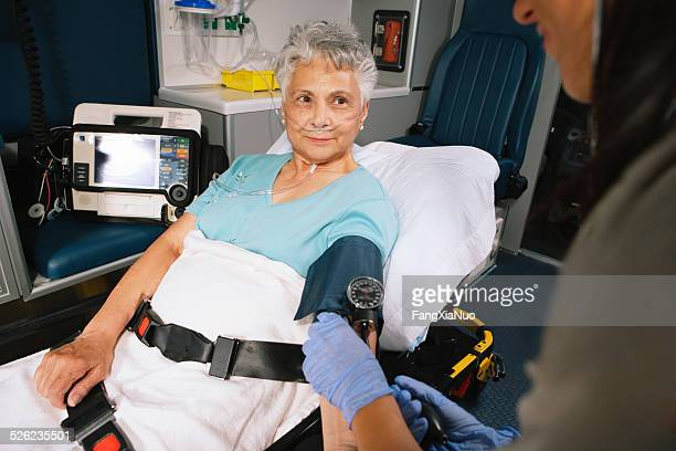 Paramedic taking patient's blood pressure in ambulance