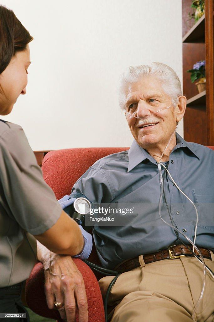 Paramedic taking senior man's blood pressure