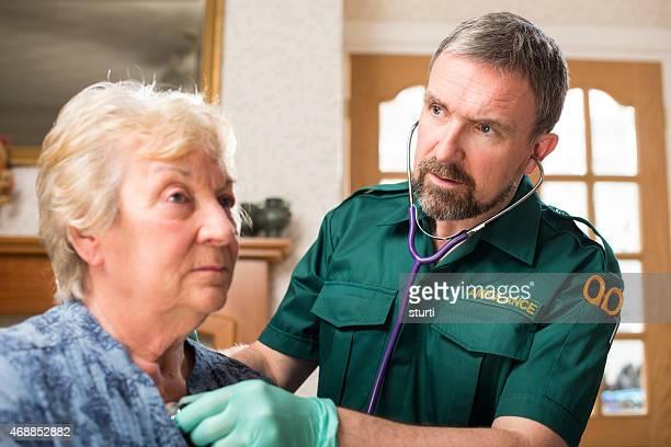 Paramedic treating senior patient at home
