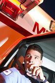 Paramedic using radio in ambulance