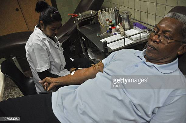 A paramedical technician takes a blood sample from a patient on December 20 2010 in a laboratory in Havana AFP PHOTO/STR