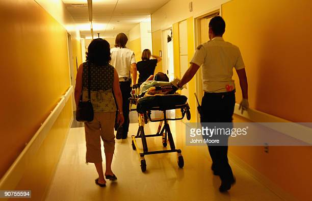 Paramedics and parents walk in an injured child into the emergency room on September 14 2009 at the nonprofit Children's Hospital in Aurora Colorado...