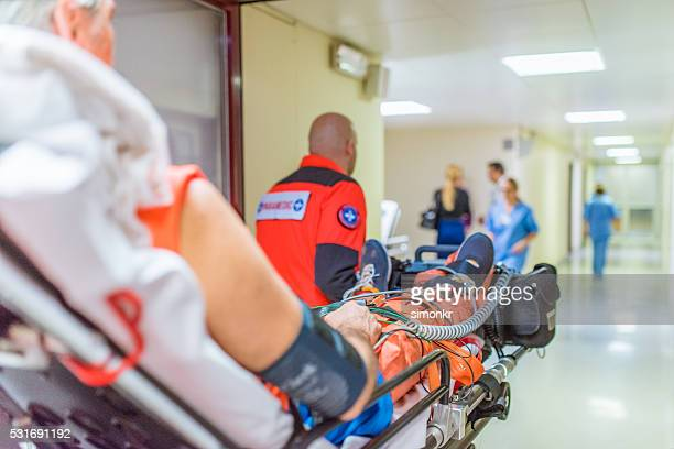 Paramedics and patient in hospital's corridor