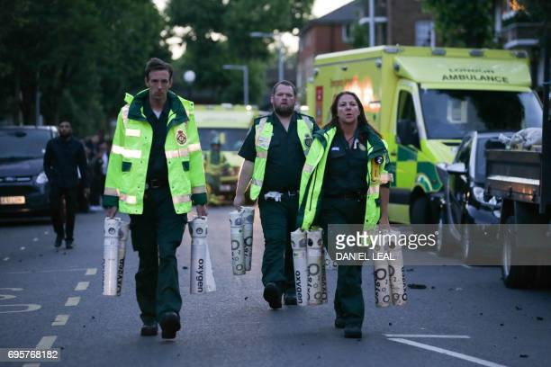 Paramedics arrive with oxygen as a huge fire engulfs the Grenfell Tower early June 14 2017 in west London The massive fire ripped through the...