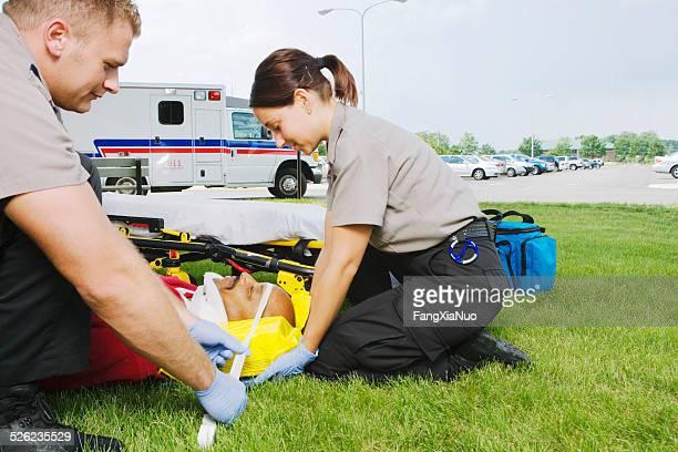 Auxiliaires médicaux fixer Minerve au patient sur de l'herbe