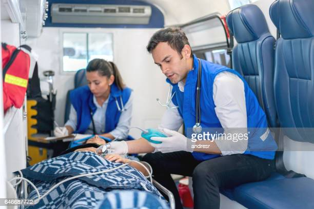 Ambulanspersonal som deltar i en patient i en ambulans
