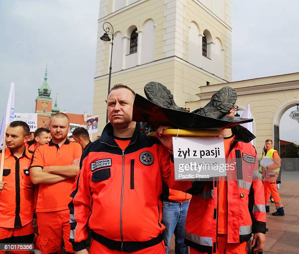 Paramedics carry a mannequin on a stretcher representing overworked and underpaid medical staff in Poland The card reading ' He lived with a passion...