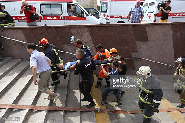 Paramedics carry a passenger injured as several subway cars derailed in Moscow on July 15 2014 in Moscow Russia At least three people have been...