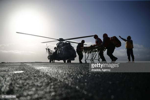 Paramedics carry a stretcher pretending to carry an injured person as part of the exercise after a Cougar AS532 helicopter landed on helipad of TCG...
