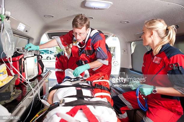 Paramedics checking patient in ambulance