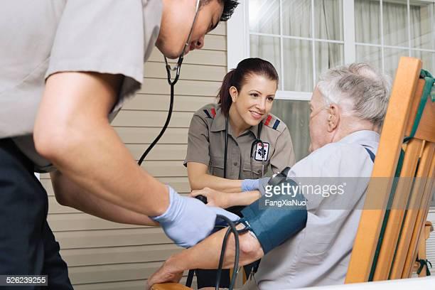 Paramedics examinar senior hombre en Porche