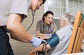 Paramedics examining senior man on porch