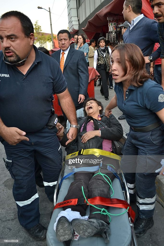 Paramedics help to workers of Pemex outside the headquarters of state-owned Mexican oil giant Pemex in Mexico City on January 31, 2013, following a blast inside the building. An explosion rocked the skyscraper, leaving up to now 14 dead and 100 injured, as a plume of black smoke billowed from the 54-floor tower, according to official sources.