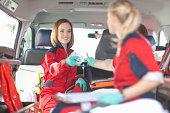 Paramedics in ambulance checking medical equipment