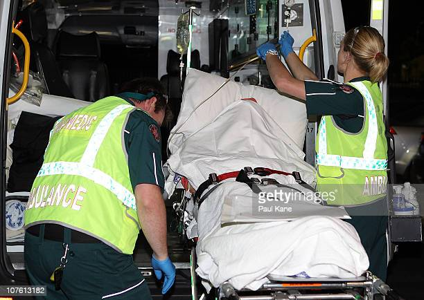 Paramedics load an injured female survivor of the Christmas Island boat wreck into an ambulance after arriving at the Perth Airport on December 16...