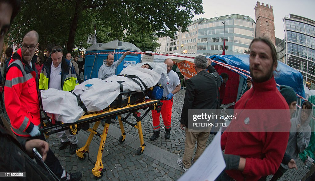 Paramedics push a refugee on a gurney on June 28, 2013 in Munich, southern Germany as he requires medical aid while being on a hunger strike to demand the right of political asylum. Several refugee protesters were taken to the hospital. OUT