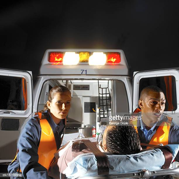 paramedics rushing a patient to the ambulance